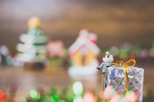 pessoa em miniatura em uma caixa de presente com decoração de celebração de Natal ao fundo