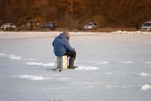 pessoa pescando no gelo com carros ao fundo em Vladivostok, Rússia foto
