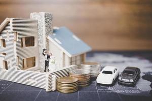 noiva e noivo em miniatura com moedas na frente de uma casa, conceito de família de sucesso