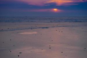 Pôr do sol nublado colorido na praia na baía de Amur em Vladivostok, Rússia foto