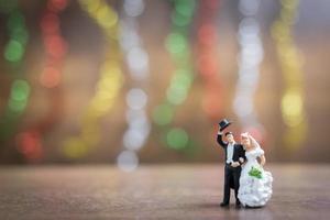 noiva e noivo em miniatura em um piso de madeira com fundo colorido bokeh, conceito de família bem-sucedido