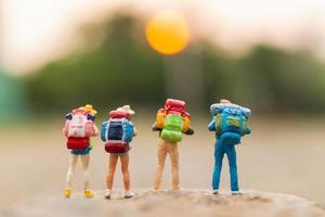 viajantes em miniatura com mochilas caminhando sobre uma rocha, conceito de viagem e aventura foto