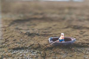 pescador em miniatura pescando em um barco foto