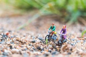 viajantes em miniatura andando de bicicleta, explorando o conceito de mundo foto