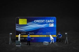polícia em miniatura e detetives em uma cena de crime com cartões de crédito, conceito de cibercrime foto