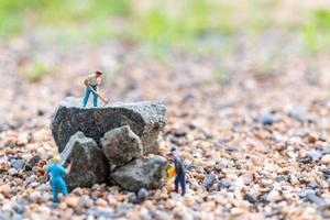 trabalhadores em miniatura sobre uma rocha, conceito de trabalho em equipe foto