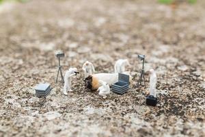 polícia em miniatura e detetives encontrando provas de cigarros antigos na cena do crime