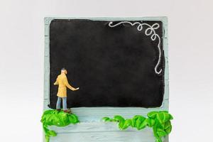 pintor em miniatura segurando um pincel no quadro-negro