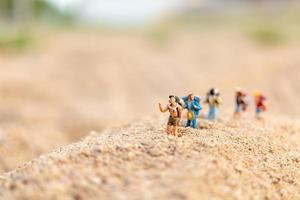 viajantes em miniatura com mochilas caminhando na areia, conceito de viagens e aventura foto