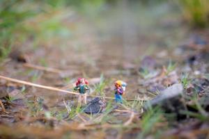 viajante em miniatura com mochilas andando no campo, conceito de viagem e aventura foto