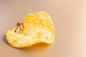trabalhador em miniatura trabalhando com batatas fritas