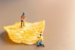 trabalhadores em miniatura trabalhando com batatas fritas