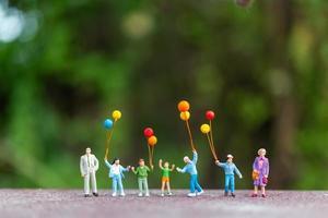 família em miniatura segurando balões coloridos, conceito de família feliz foto