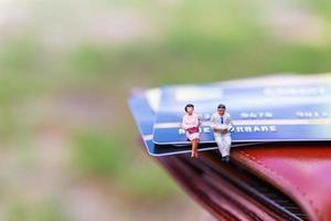 empresários em miniatura sentados sobre conceitos de cartão de crédito, negócios e finanças
