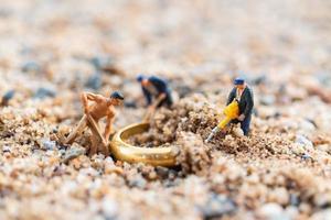 trabalhadores em miniatura cavando anéis de ouro na areia, conceito de crescimento do negócio foto