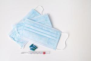máscara cirúrgica, cápsulas medicinais e termômetro