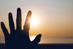 silhueta da mão estende-se para o céu do pôr do sol foto