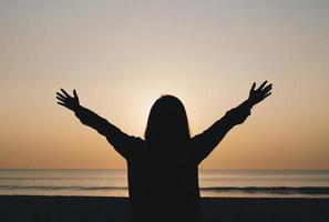 silhueta de mulher de braços abertos na praia