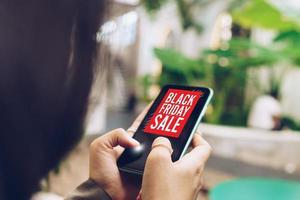 mulher usando um smartphone faz venda on-line na liquidação de sexta-feira negra