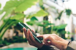 mão de uma mulher usando smartphone para fazer negócios, redes sociais, comunicação