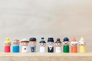 bonecos de madeira em miniatura com rostos felizes em um fundo de madeira foto