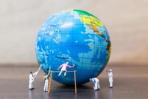 pintores em miniatura pintando em um globo com um fundo de madeira, o conceito de salvar a terra foto