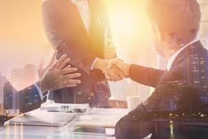 dupla exposição de empresários apertando as mãos contra o horizonte da cidade