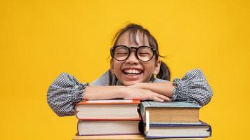 aluna tailandesa de óculos, apoiada na pilha de livros, sorrindo e olhando para a câmera com fundo amarelo