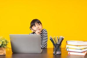 menina asiática com pose de pensamento sentada com laptop, livros e lápis em uma mesa de madeira com fundo amarelo