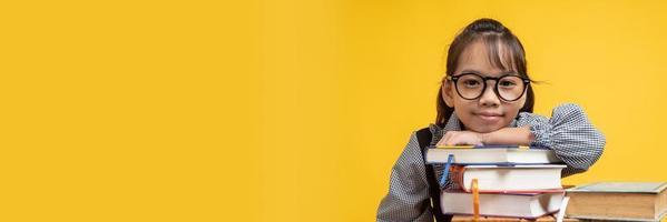 menina asiática tailandesa de óculos, encostada na pilha de livros e olhando a câmera com fundo amarelo