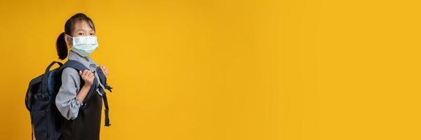 jovem tailandesa usando uma mochila e olhando a câmera com fundo amarelo