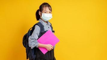 jovem tailandesa usando máscara, segurando livros, usando uma mochila e olhando para o fundo amarelo da câmera