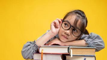 jovem tailandesa encostada na pilha de livros, tocando seus óculos e pensando em estúdio com fundo amarelo