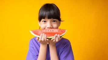 jovem menina asiática sorrindo com camisa roxa segurando uma fatia de melancia em estúdio com fundo amarelo