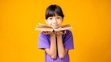 jovem garota asiática sorrindo de camisa roxa segurando um livro aberto no estúdio com fundo amarelo