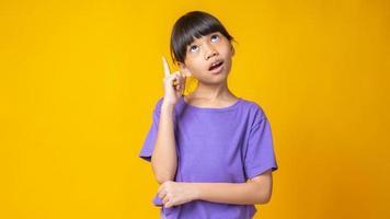 jovem garota asiática de camisa roxa apontando para cima e pensando em estúdio com fundo amarelo