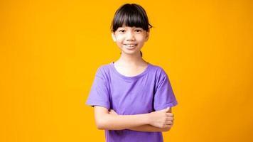 jovem asiática de camisa roxa sorrindo com os braços cruzados no estúdio com fundo amarelo
