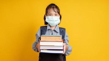 jovem tailandesa usando máscara e segurando uma pilha de livros em um estúdio com fundo amarelo