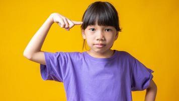 jovem garota asiática com camisa violeta apontando para a cabeça isolada em estúdio com fundo amarelo foto