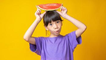 jovem asiática segurando uma fatia de melancia na cabeça, olhando para a câmera no estúdio com o fundo