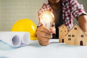 homem segurando uma lâmpada acesa ao lado de modelos de casas, papéis enrolados e um capacete foto