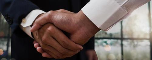 close-up de empresários apertando as mãos com janela desfocada ao fundo foto