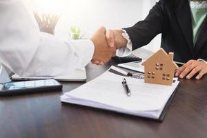 duas pessoas apertam as mãos ao lado de um modelo de casa e um contrato
