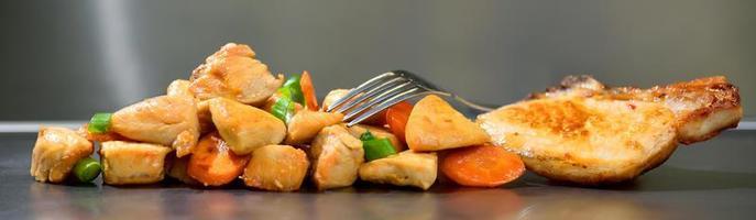 Fatias de frango assado temperado com cenoura e alho-poró em fundo de aço inoxidável