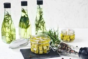 queijo feta marinado em uma jarra de vidro, especiarias e azeite de oliva aromatizado em um fundo de madeira foto