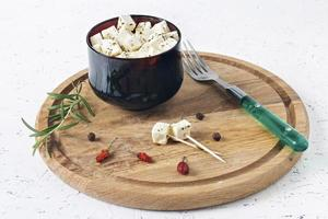 queijo feta marinado em um prato sobre uma placa de madeira com especiarias em um fundo branco foto