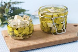queijo feta marinado em uma jarra de vidro e especiarias contra um fundo azul foto