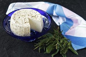 queijo branco em um prato em um fundo preto e guardanapo foto