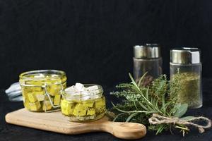 queijo feta marinado em uma jarra de vidro e especiarias em um fundo preto foto