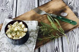 queijo feta marinado em um prato sobre uma placa de madeira sobre um fundo de madeira foto